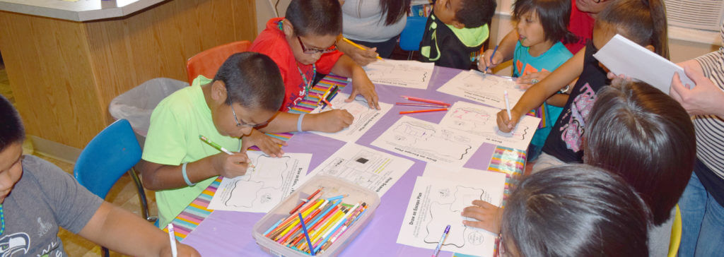 Children at the Burns Paiute Tribe youth group sit at a table and complete an activity for Health Half Hour.