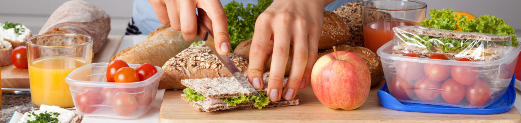 A person cutting a sandwich while making a healthy lunch