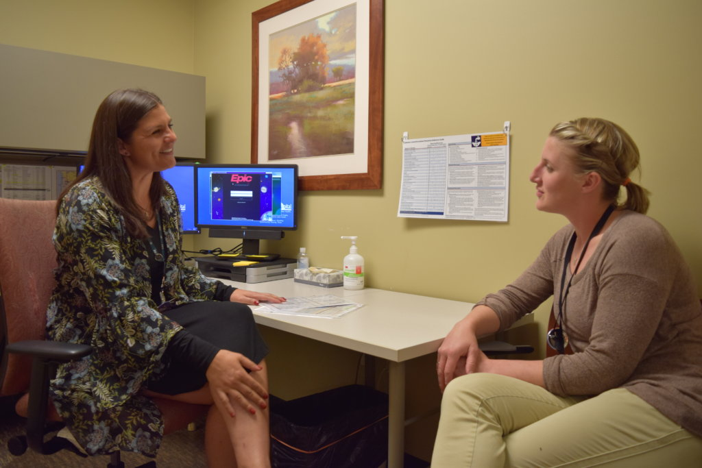 HDH caregivers converse in front of a computer screen displaying the Epic electronic health record login.